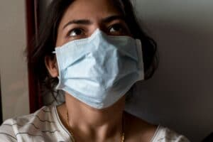 A mental health pandemic is following COVID-19, which required this woman to wear a mask.